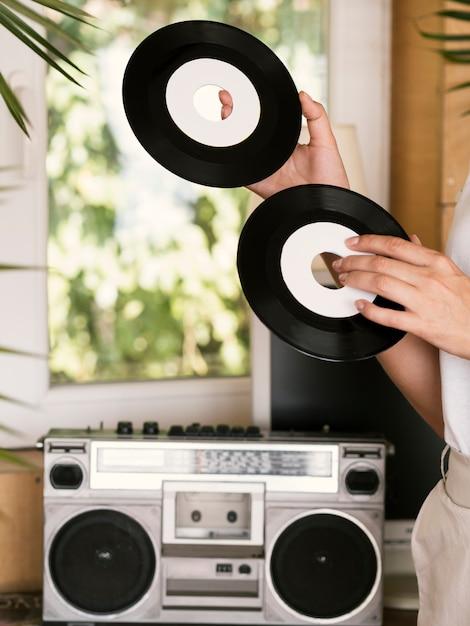 Jonge persoon die uitstekende vinylverslagen binnen houdt Gratis Foto