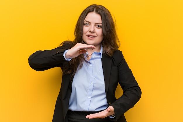 Jonge plus grootte kaukasische bedrijfsvrouw die iets met beide handen houdt, productpresentatie. Premium Foto