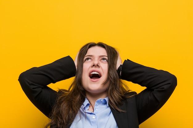 Jonge plus size blanke vrouw die oren bedekt met handen proberen niet te hard geluid te horen. Premium Foto