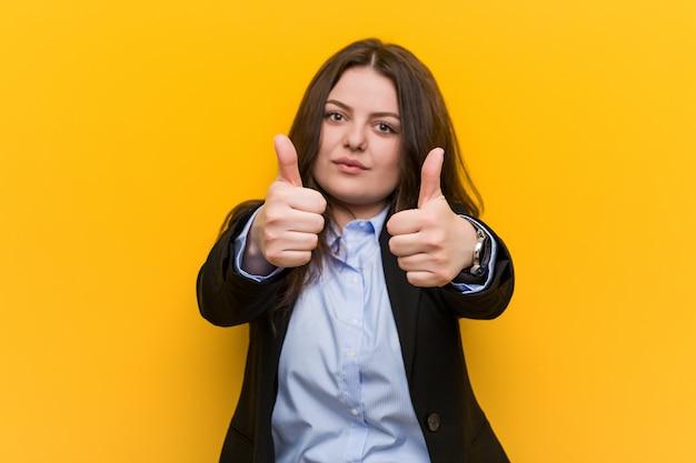 Jonge plus size blanke zakenvrouw met thumbs ups, proost over iets, steun en respect. Premium Foto