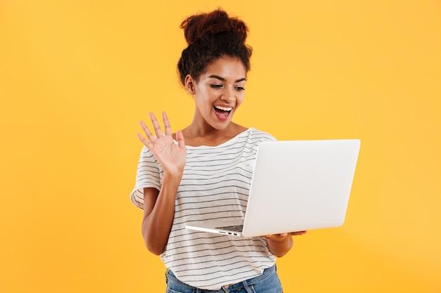 Jonge positieve koele dame met krullend haar dat geïsoleerde laptop met behulp van Gratis Foto