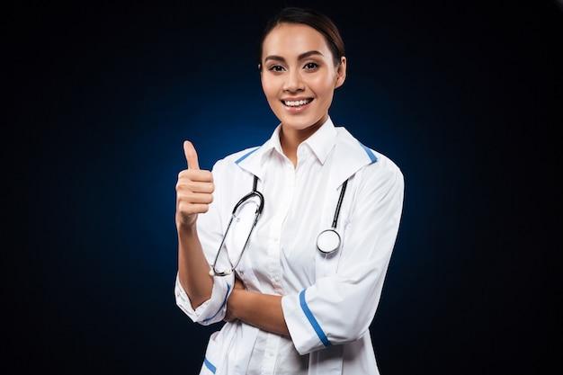Jonge positieve vrouw arts met stethoscoop die duim toont Gratis Foto
