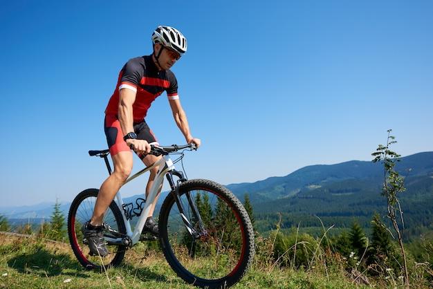 Jonge professionele fietser berijdende fiets op grasrijke heuvel. bergen en blauwe zomer hemel. actieve levensstijl en extreme sport concept Premium Foto