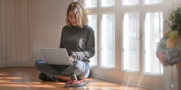 Jonge professionele freelancer werkt aan haar project tijdens de vergadering in de buurt van de ramen Premium Foto
