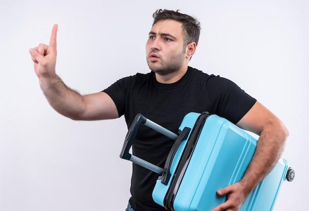 Jonge reiziger man in zwart t-shirt bedrijf koffer gebaren wacht een minuut met hand kijken met ernstige uitdrukking staande over witte muur Gratis Foto