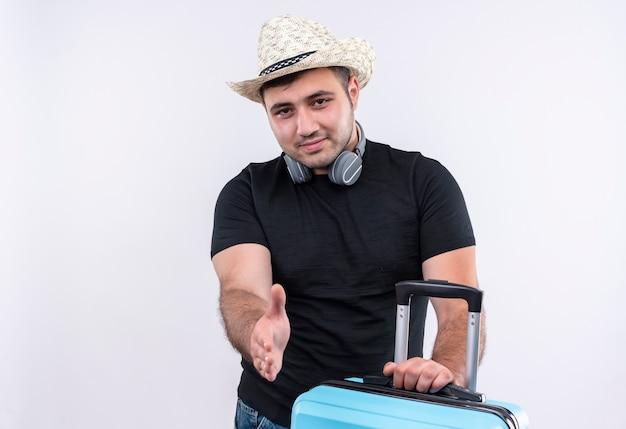 Jonge reiziger man in zwart t-shirt en zomerhoed met koffer op zoek naar zelfverzekerde groet met hand staande over witte muur Gratis Foto