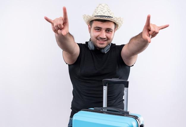 Jonge reiziger man in zwart t-shirt en zomerhoed met koffer rock symbolen met vingers glimlachend vrolijk staande over witte muur maken Gratis Foto