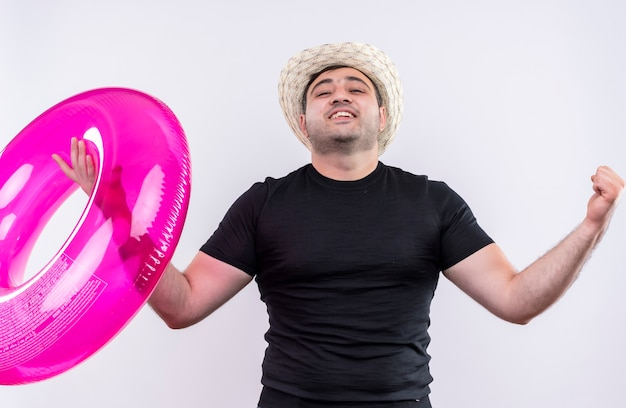 Jonge reiziger man in zwart t-shirt en zomerhoed met opblaasbare ring gebalde vuisten verheugend zijn succes staande over witte muur Gratis Foto