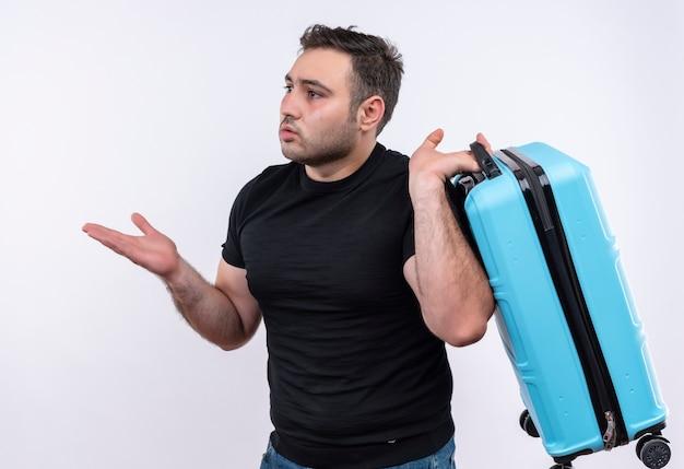 Jonge reiziger man in zwart t-shirt met koffer opzij kijken verward en erg angstig staande over witte muur Gratis Foto