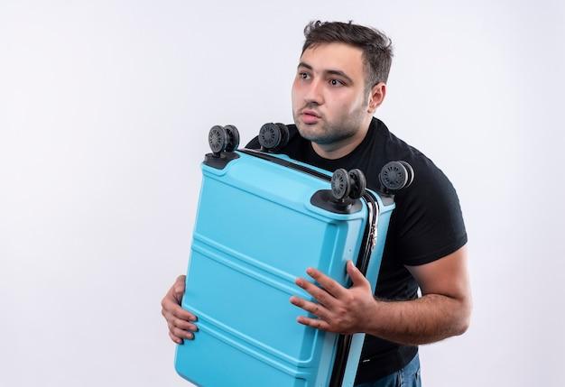 Jonge reiziger man in zwarte t-shirt bedrijf koffer opzij kijken verward en bezorgd staande over witte muur Gratis Foto
