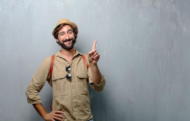Jonge reiziger man of toerist glimlachend en op zoek tevreden en gelukkig, nummer één Premium Foto