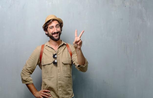 Jonge reiziger man of toerist glimlachend en op zoek tevreden en happy.number twee Premium Foto