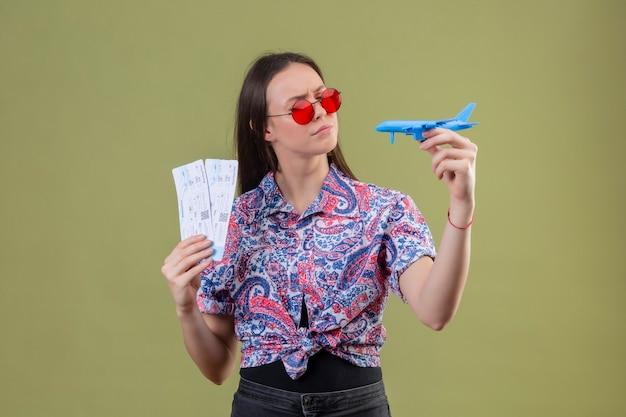 Jonge reiziger vrouw draagt ?? rode zonnebril met kaartjes en speelgoed vliegtuig te kijken met peinzende uitdrukking met fronsend gezicht staande over groene achtergrond Gratis Foto
