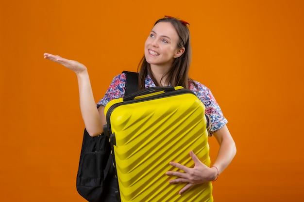 Jonge reiziger vrouw dragen rode zonnebril op hoofd staande met rugzak bedrijf koffer opzij kijken en presenteren met arm van de hand iets glimlachend met blij gezicht over oranje pagina Gratis Foto