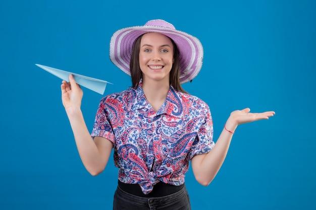 Jonge reiziger vrouw in zomer hoed bedrijf papieren vliegtuigje presenteren met arm van de hand kijken camera glimlachend vrolijk met blij gezicht staande over blauwe achtergrond Gratis Foto