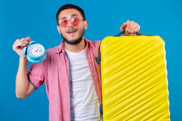 Jonge reizigers knappe kerel die zonnebril dragen die reiskoffer en wekker houden kijkend gelukkige en positieve status over blauwe achtergrond Gratis Foto