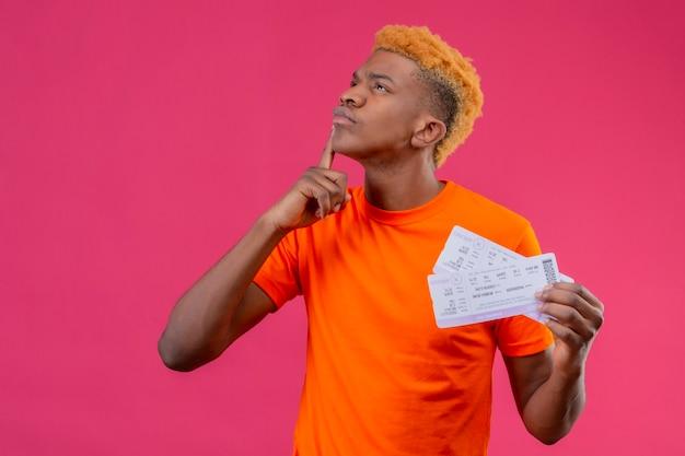 Jonge reizigersjongen die oranje t-shirt draagt die vliegtuigkaartjes houdt die met vinger op kin met peinzende uitdrukking op gezicht opkijken die zich over roze muur bevindt Gratis Foto
