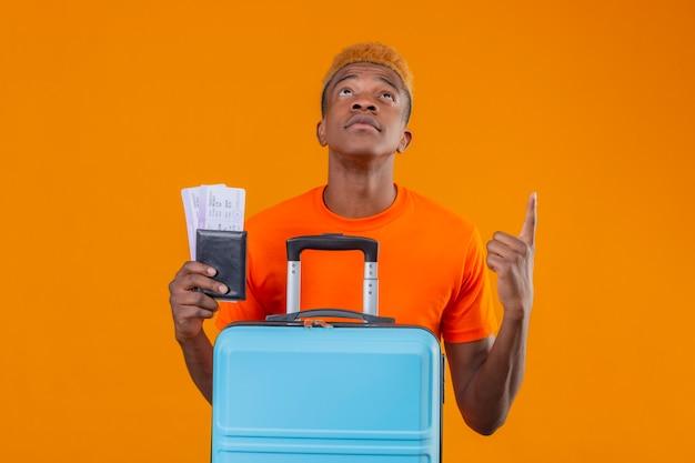 Jonge reizigersjongen die oranje t-shirt draagt die vliegtuigtickets en koffer houdt die omhoog kijkt wijzend naar iets met ernstig gezicht dat zich over oranje muur bevindt Gratis Foto