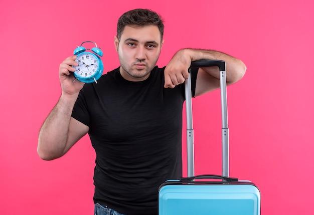 Jonge reizigersmens in de zwarte koffer en de wekker van de t-shirtholding met zelfverzekerde ernstige uitdrukking die zich over roze muur bevindt Gratis Foto