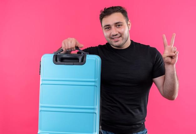 Jonge reizigersmens in de zwarte koffer van de t-shirtholding gelukkig en positief met glimlach op gezicht die overwinningsteken tonen dat zich over roze muur bevindt Gratis Foto
