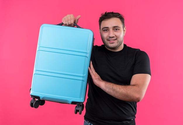 Jonge reizigersmens in de zwarte koffer van de t-shirtholding gelukkig en positief met glimlach op gezicht die zich over roze muur bevinden Gratis Foto