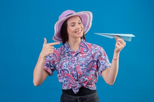 Jonge reizigersvrouw die in de holdingsdocument van de de zomerhoed vliegtuig die met vinger aan het richten glimlachen met gelukkig gezicht over blauwe muur Gratis Foto