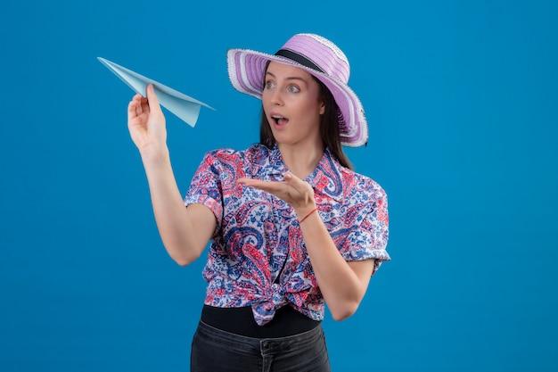 Jonge reizigersvrouw die in de holdingsdocument van de de zomerhoed vliegtuig met wapen van hand aan het kijken die verrast over blauwe muur kijken Gratis Foto