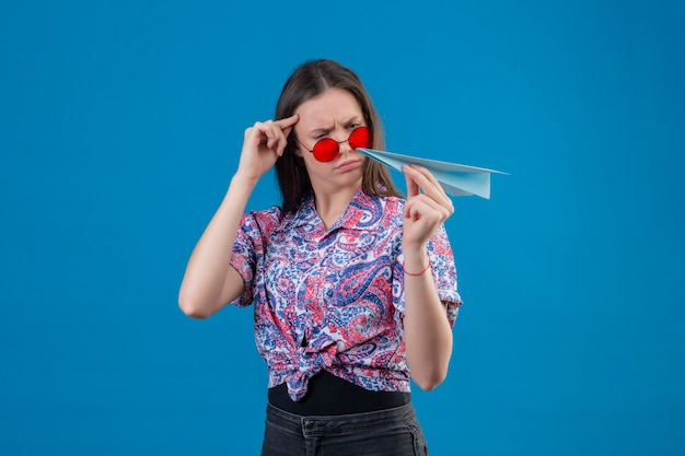 Jonge reizigersvrouw die rode zonnebril dragen die document vliegtuig houden bekijkend het met fronsend ontstemd gezicht twijfelend over blauwe muur Gratis Foto