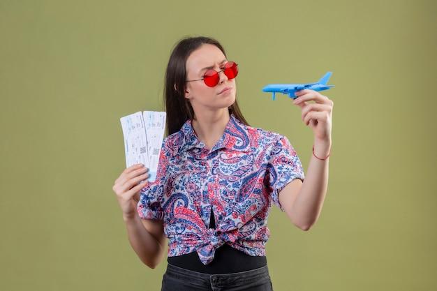 Jonge reizigersvrouw die rode zonnebril dragen die kaartjes en stuk speelgoed vliegtuig houden die het met peinzende uitdrukking met fronsend gezicht over groene muur bekijken Gratis Foto