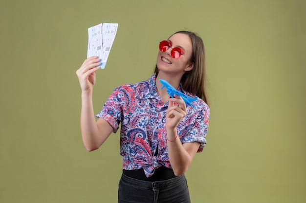 Jonge reizigersvrouw die rode zonnebril dragen die kaartjes en stuk speelgoed vliegtuig houden die opzij met gelukkig gezicht kijken die vrolijk over groene muur glimlachen Gratis Foto