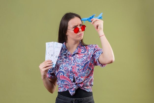 Jonge reizigersvrouw die rode zonnebril dragen die kaartjes en stuk speelgoed vliegtuig houden die opzij met peinzende uitdrukking met fronsend gezicht over groene muur kijken Gratis Foto