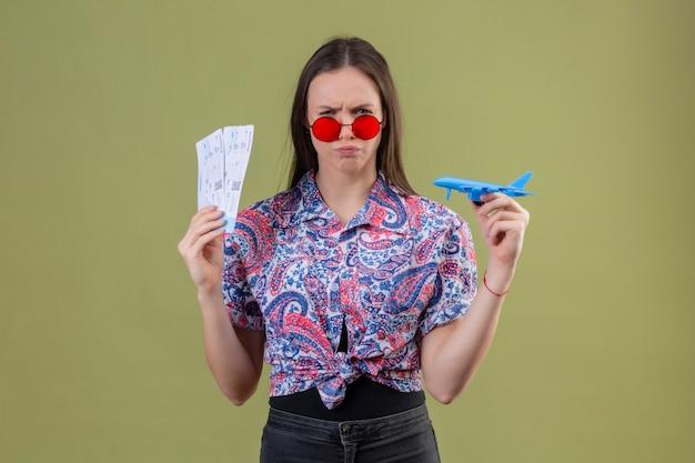 Jonge reizigersvrouw die rode zonnebril dragen die kaartjes en stuk speelgoed vliegtuig met fronsend gezicht houden over groene muur ontevreden Gratis Foto