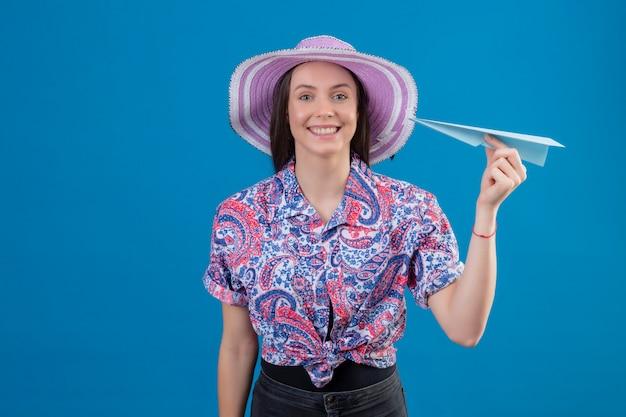 Jonge reizigersvrouw in de holdingsdocument van de de zomerhoed vliegtuig positief en het gelukkige vrolijk glimlachen over blauwe muur Gratis Foto