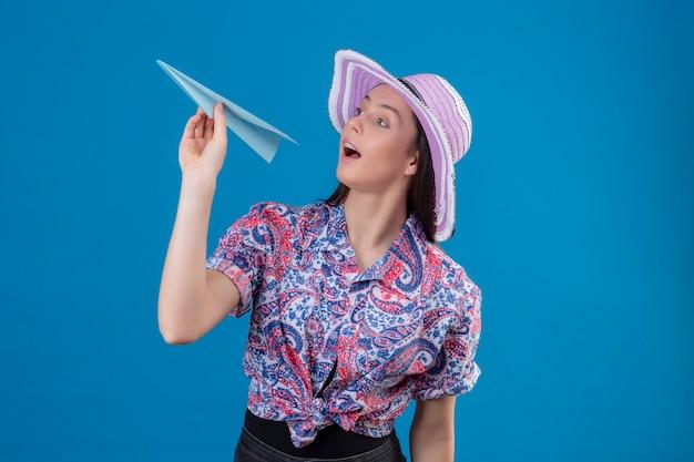 Jonge reizigersvrouw in de holdingsdocument vliegtuig van de de zomerhoed speels en gelukkig status over blauwe achtergrond Gratis Foto