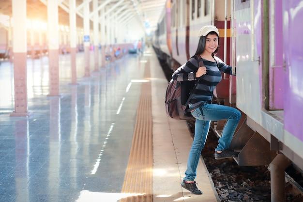 Jonge reizigersvrouw met rugzak die op de trein krijgen Premium Foto