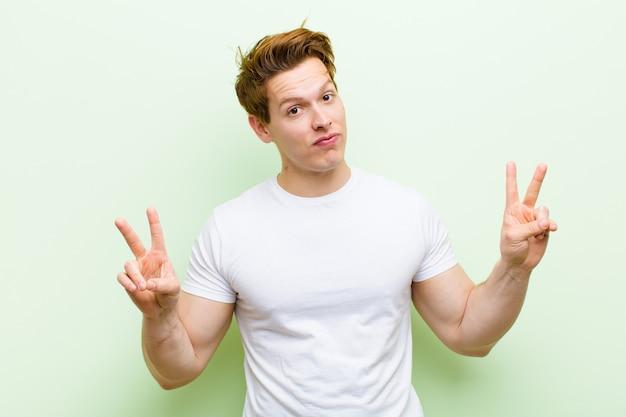Jonge rode hoofd knappe man glimlachend en op zoek gelukkig, vriendelijk en tevreden, gebaren overwinning of vrede met beide handen Premium Foto