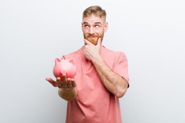 Jonge rode hoofdmens die een spaarvarken houdt tegen witte achtergrond Premium Foto