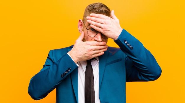 Jonge rode hoofdzakenman die gezicht behandelt met beide handen die nee zeggen tegen de camera! afbeeldingen weigeren oranje foto's verbieden Premium Foto