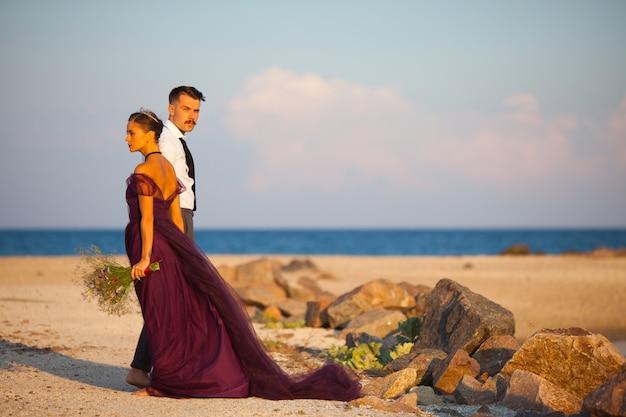 Jonge romantische paar ontspannen op het strand kijken naar de zonsondergang Gratis Foto