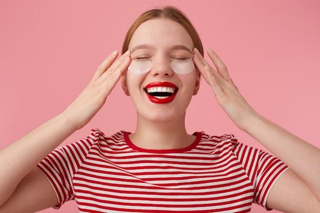 Jonge roodharige dame met rode lippen draagt een rood gestreept t-shirt, met vlekken onder de ogen, masseert tempels, geniet van vrije tijd voor zelfzorg, breed glimlachend. staat. Gratis Foto