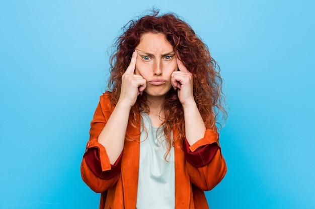 Jonge roodharige elegante vrouw gericht op een taak, wijsvingers hoofd houden. Premium Foto