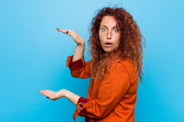 Jonge roodharige elegante vrouw geschokt en verbaasd met een kopie ruimte tussen handen. Premium Foto