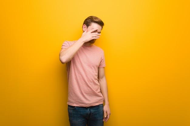 Jonge roodharige man beschaamd en tegelijkertijd lachen Premium Foto