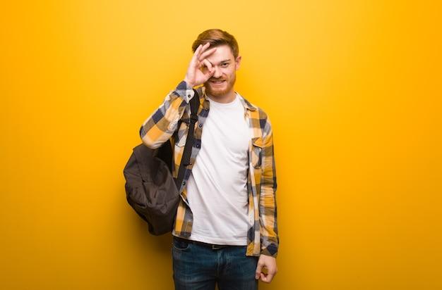 Jonge roodharige student man zelfverzekerd doen ok gebaar op oog Premium Foto
