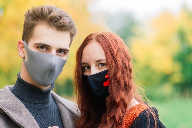 Jonge roodharige vrouw en vriend die medische maskers dragen Premium Foto