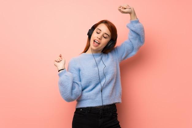 Jonge roodharige vrouw over roze muur luisteren naar muziek met een koptelefoon en dansen Premium Foto