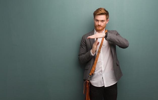 Jonge roodharige zakenman doet een time-out gebaar Premium Foto