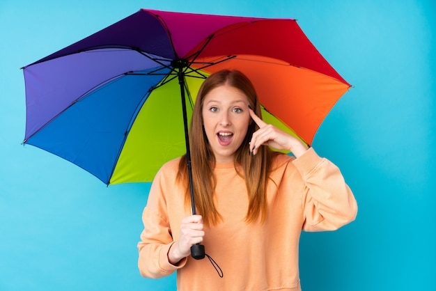 Jonge roodharigevrouw die een paraplu over geïsoleerde muur houden van plan om de oplossing te realiseren Premium Foto