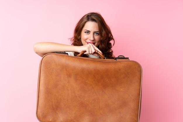 Jonge russische vrouw over geïsoleerde roze achtergrond die een uitstekende aktentas houdt Premium Foto