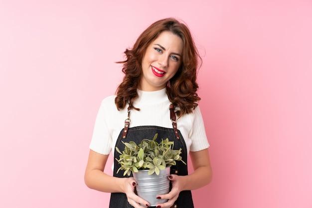 Jonge russische vrouw over geïsoleerde roze die een bloempot neemt Premium Foto